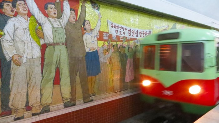 Train rattles past a workers mural at a Pyongyang Subway station