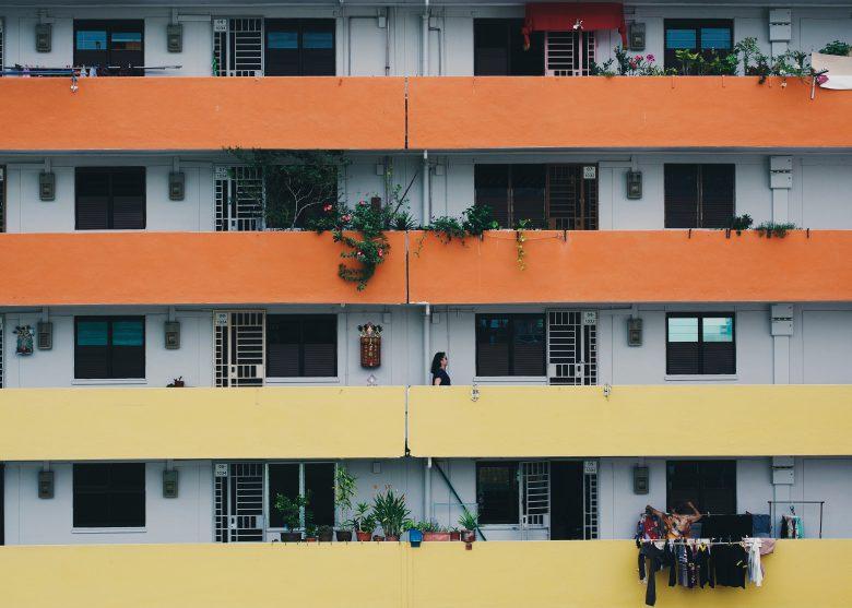 A lady walks on an colourful HDB balcony in Singapore