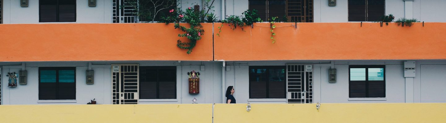 A lady walks on an colourful HDB balcony in Singapore